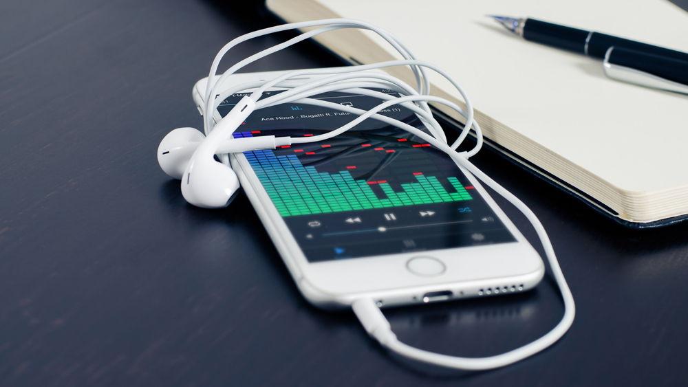 iPhone с наушниками и музыкой