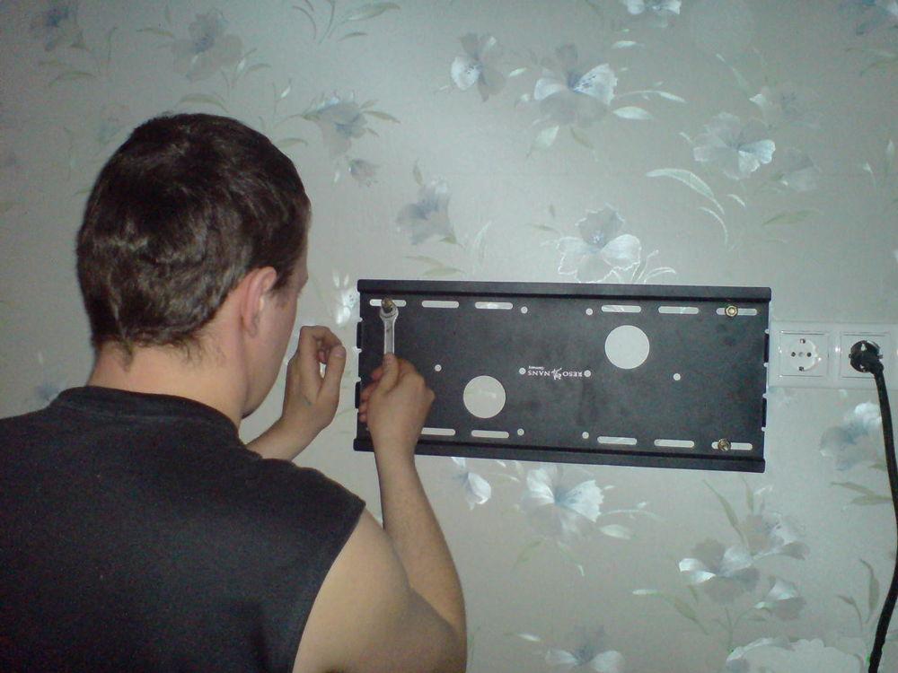 Мужчина устанавливает кронштейн для телевизора на стену
