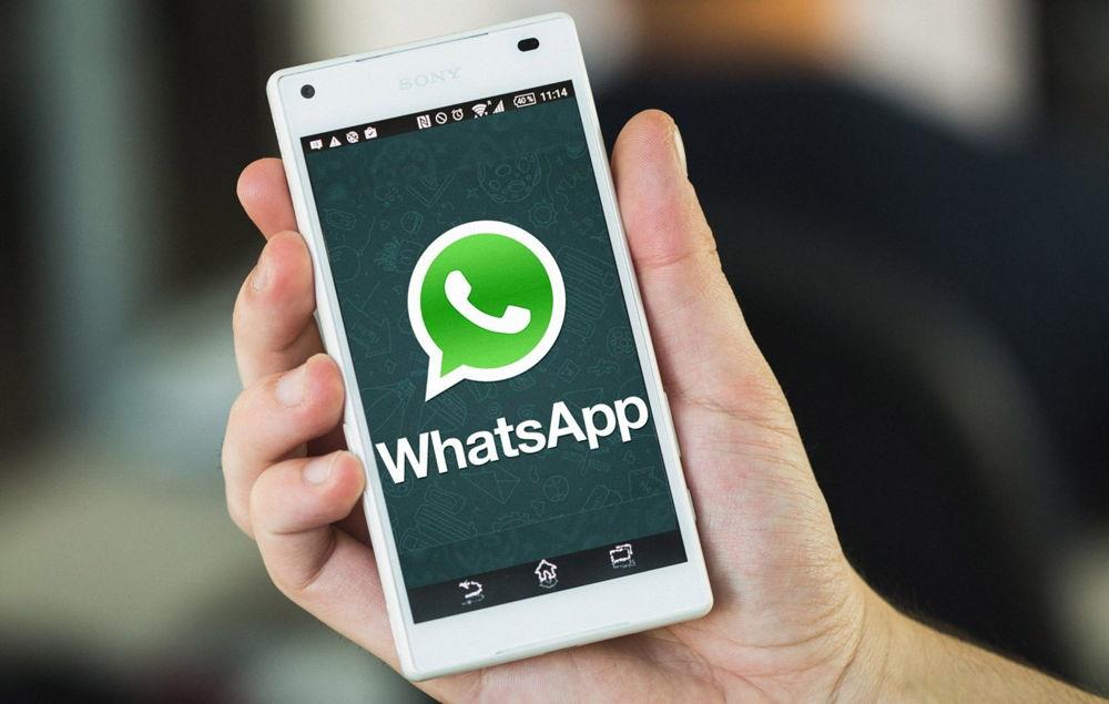 Белый телефон в руке с WhatsApp