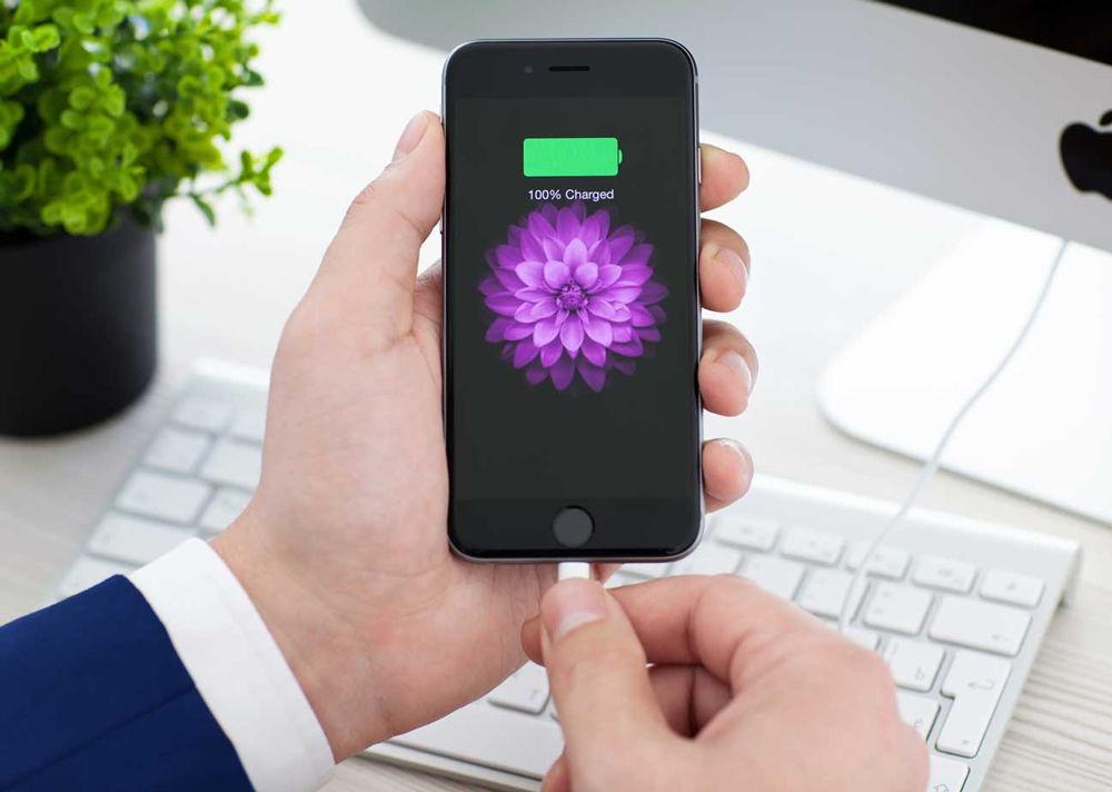 Мужчина держит заряженный iPhone в руке