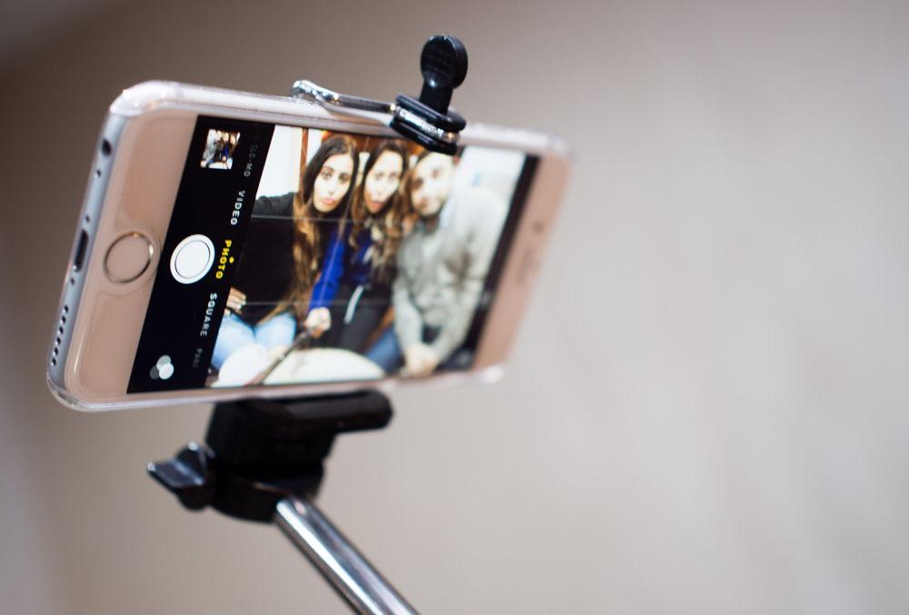 Белый iPhone закреплен в моноподе